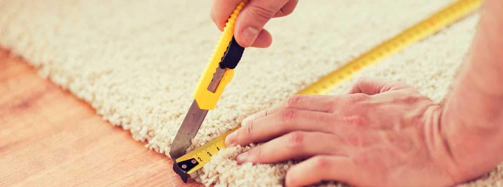 Flooring installer measuring carpeting