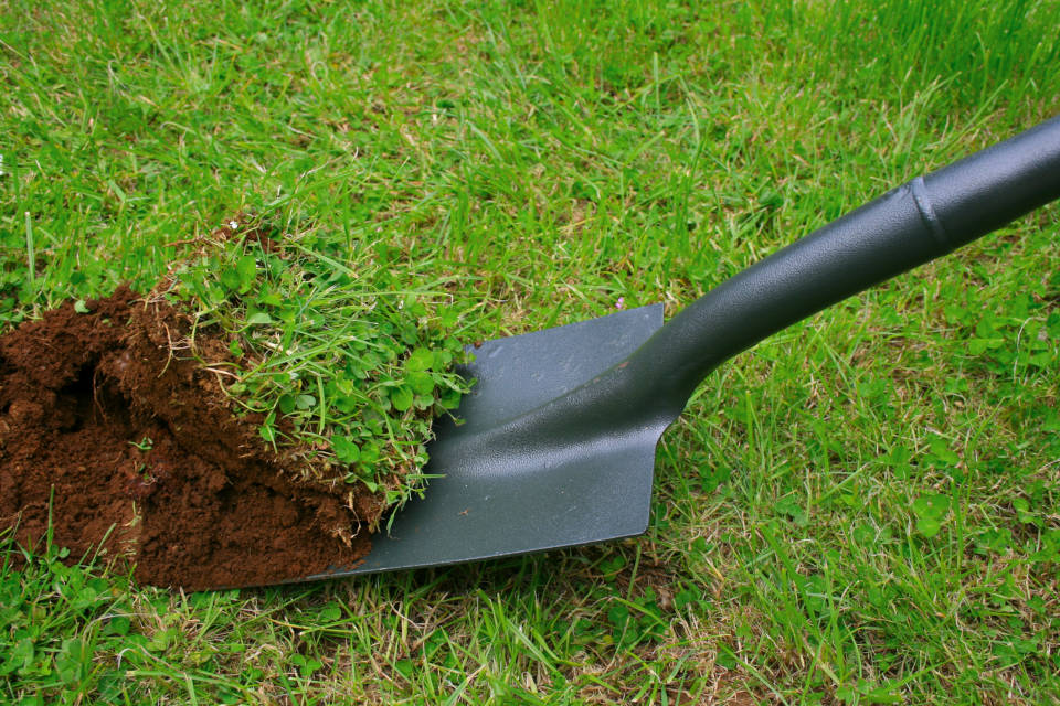Excavate for a patio using a shovel and then tamp the surface