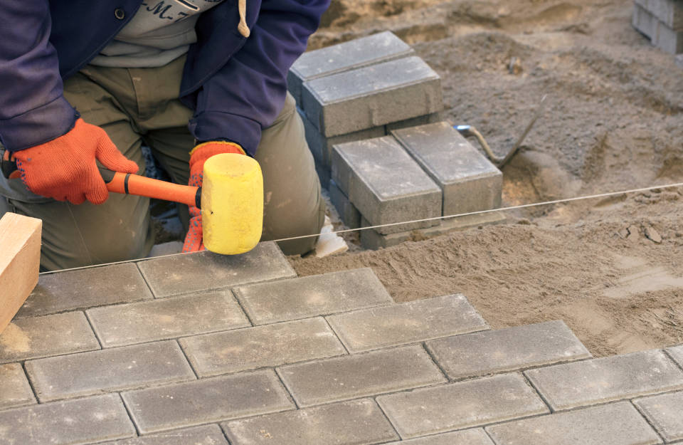 Setting pavers evenly into sand base