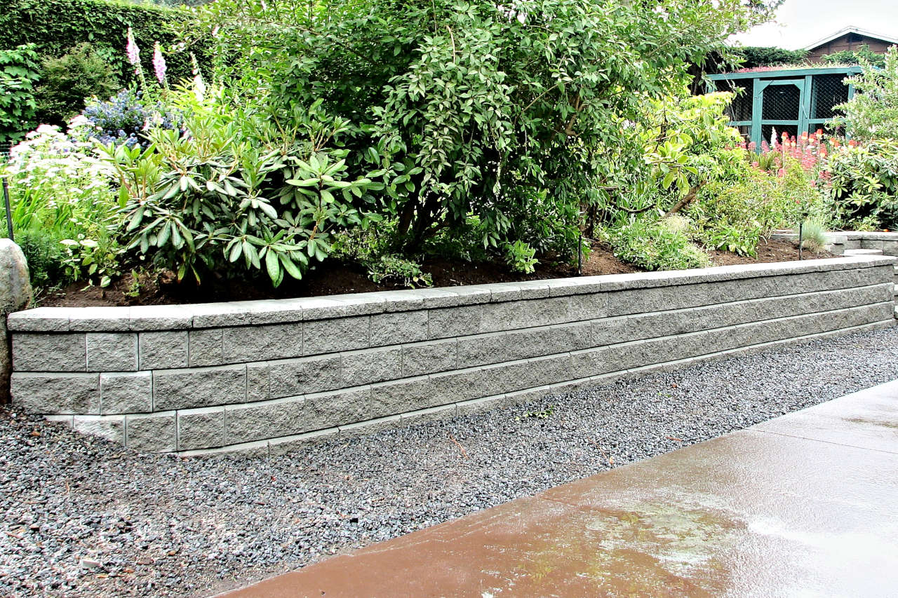 new block retaining wall with plants and shrubs above
