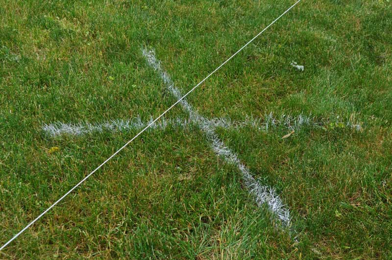 "Mason line attached to stakes and an ""x"" drawn with layout paint"