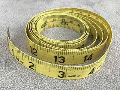 sewing tape measure coiled up showing measurement markings