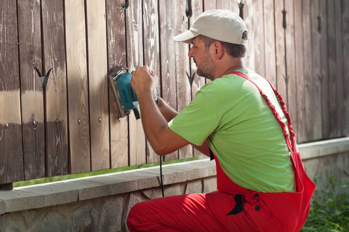 Painter prepping a fence for stain by sanding the surface
