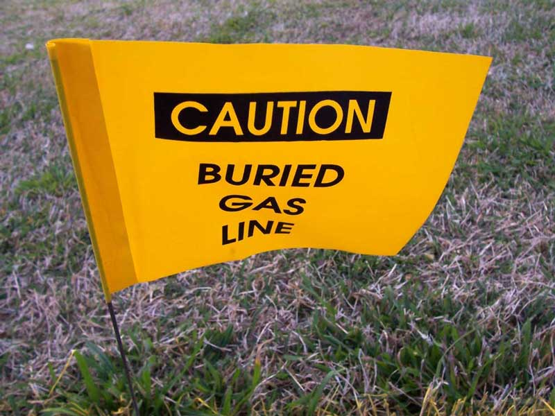 warning flag indicating a gas line is buried beneath the ground