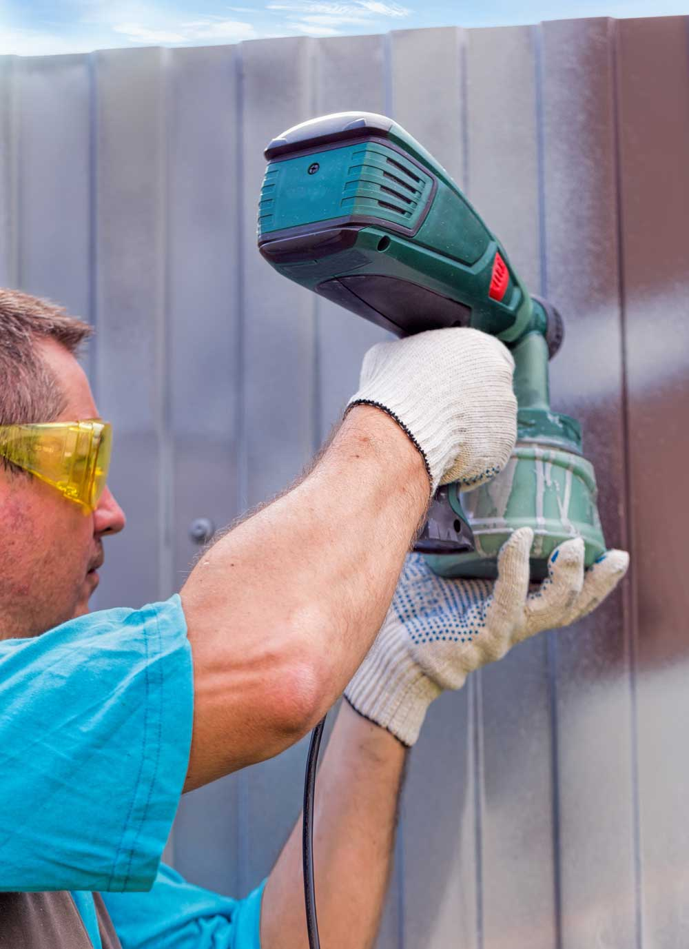 Painter applying stain to a fence using a paint sprayer