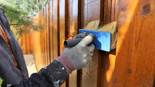 Painter applying stain to a fence using a brush