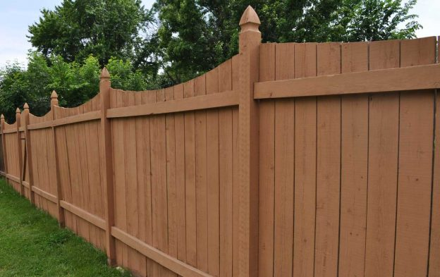 A newly installed wood privacy fence with a scallop detail