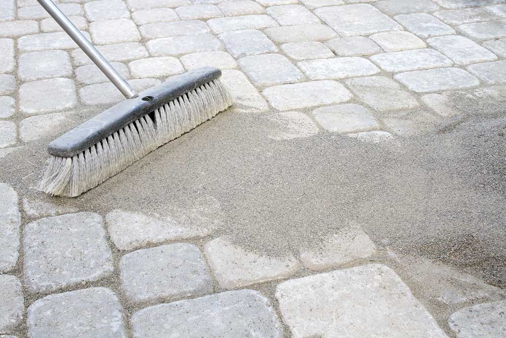 Sweep polymeric jointing sand into paver joints to prevent weed growth