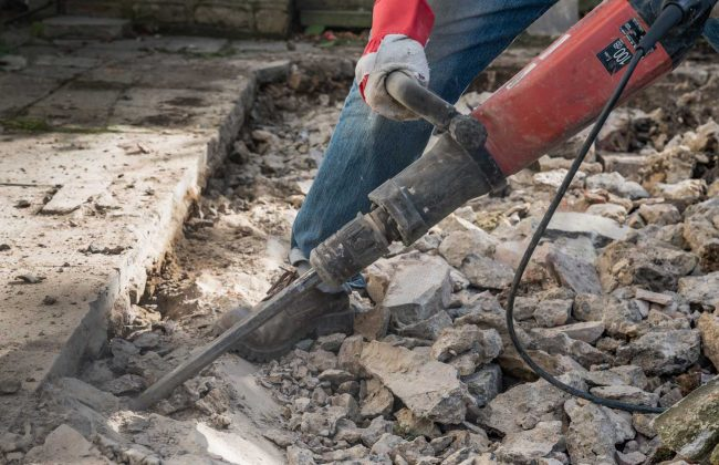 contractor demolishing and removing a concrete slab