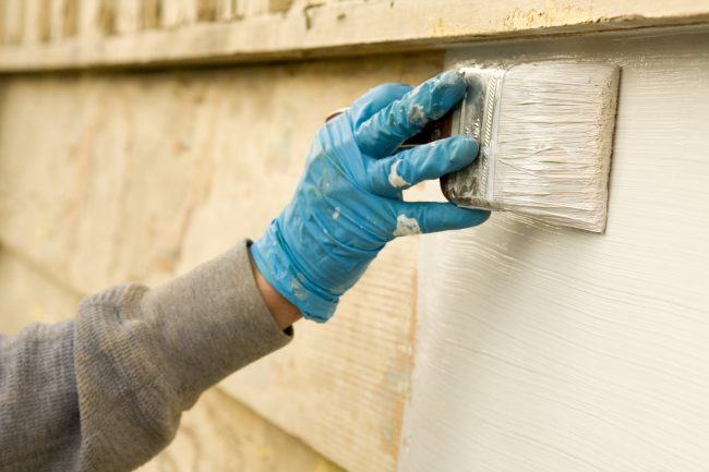 contractor painting the siding of a home