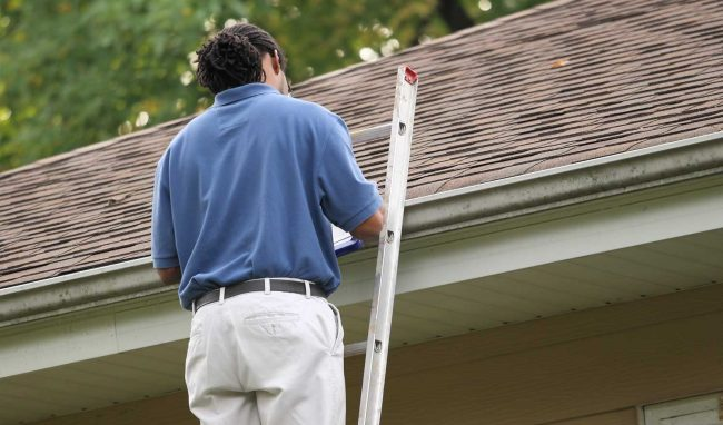 Inspector examining a roof for concerns or needed repairs