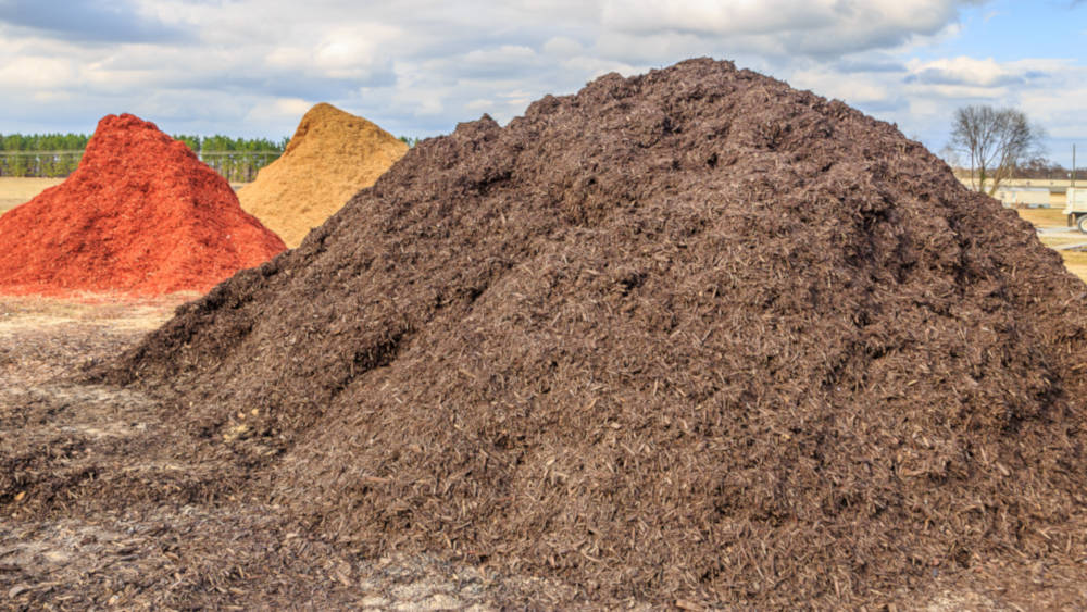Large piles of landscaping material, including soil and mulch