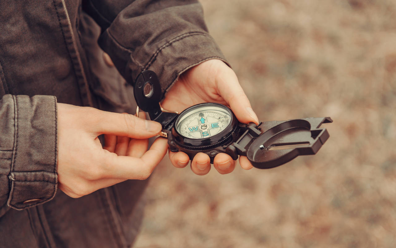 Person holding a compass to locate property lines defined in a deed's legal description