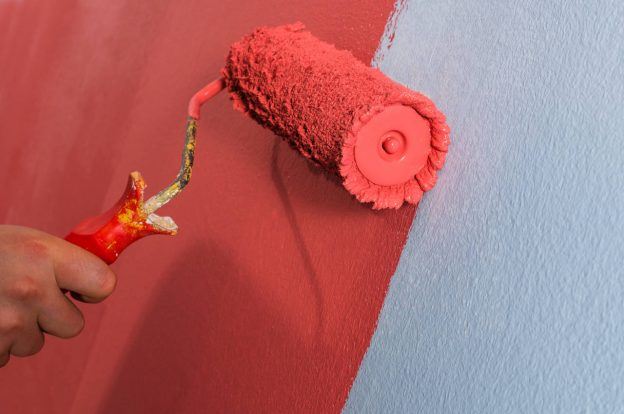 Using a roller to paint a wall with red paint