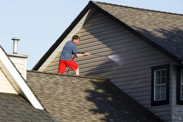 Man power-washing the siding of a home.