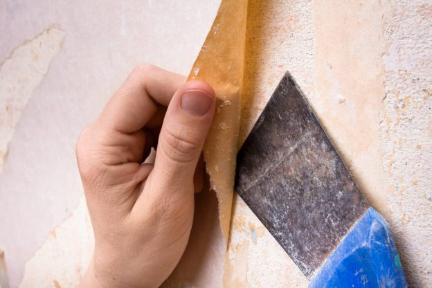 Person removing wallpaper using a scraper
