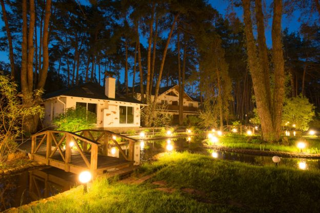 Outdoor landscape lights surrounding a home at dusk
