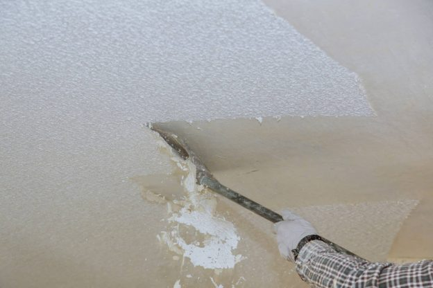Contractor scraping a ceiling to remove the popcorn texture