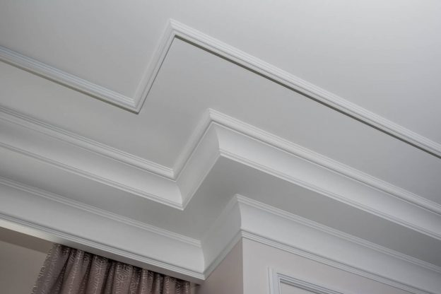 Crown molding installed near a window curtain pocket composed of several layers of trim
