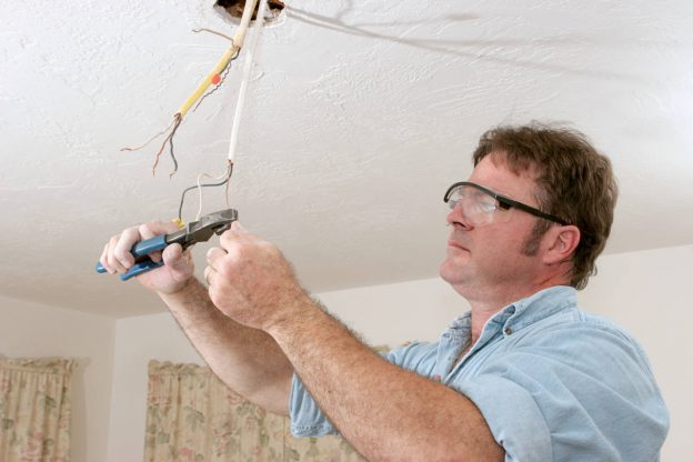 Electrician rewiring a light fixture