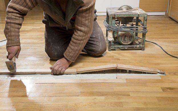 carpenter repairing a hardwood floor