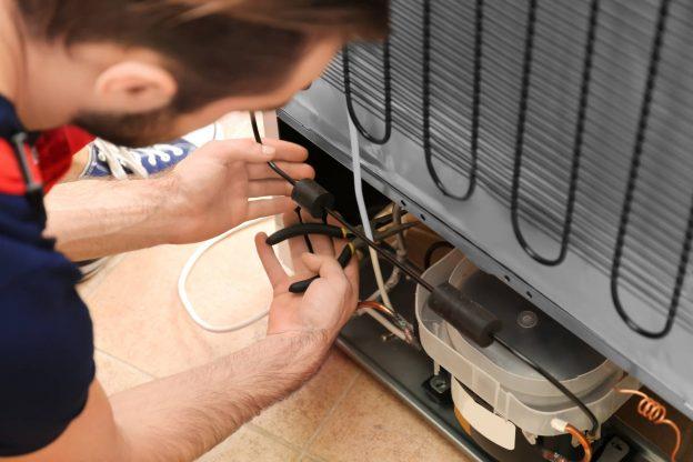 Technician repairing a refrigerator