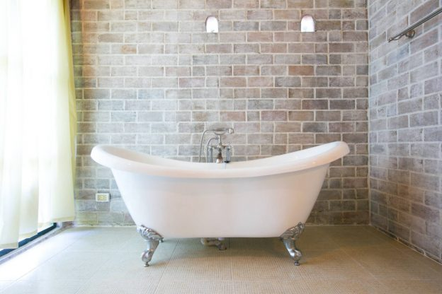 cast iron clawfoot bathtub in a bathroom with brick walls