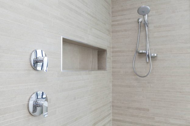 tile shower with cubby, shower head, and controls