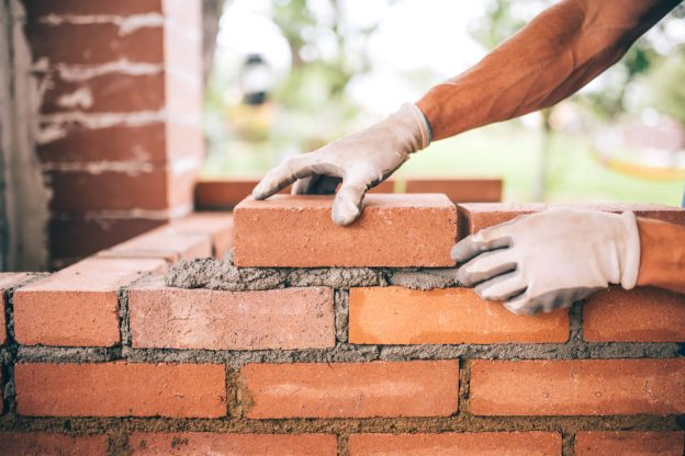 Mason installing a brick wall