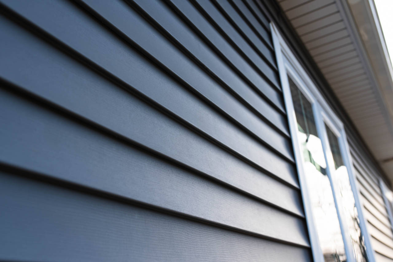 Using a utility trim and j-channel for vinyl siding at the top of the wall beneath the soffit