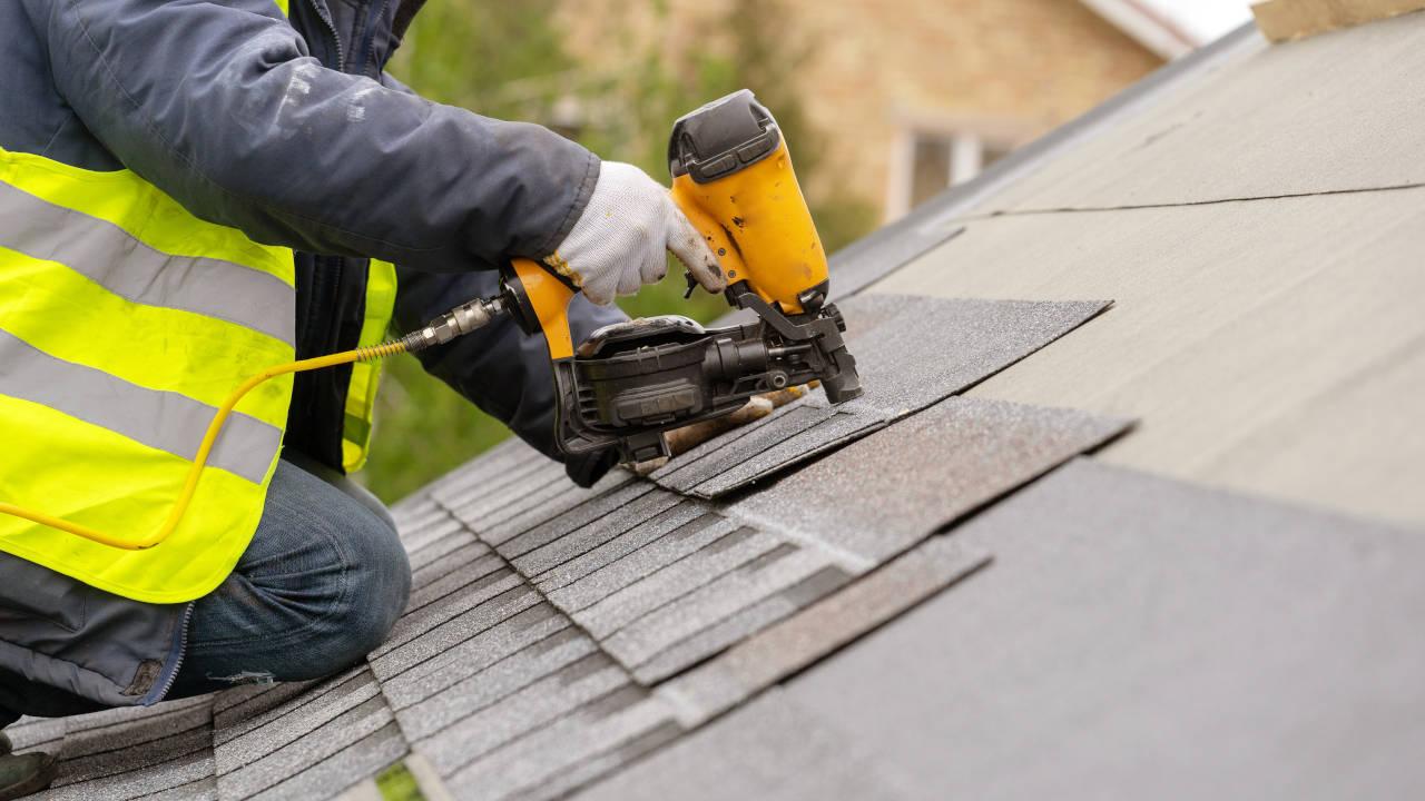 Contractors install an asphalt shingle roof