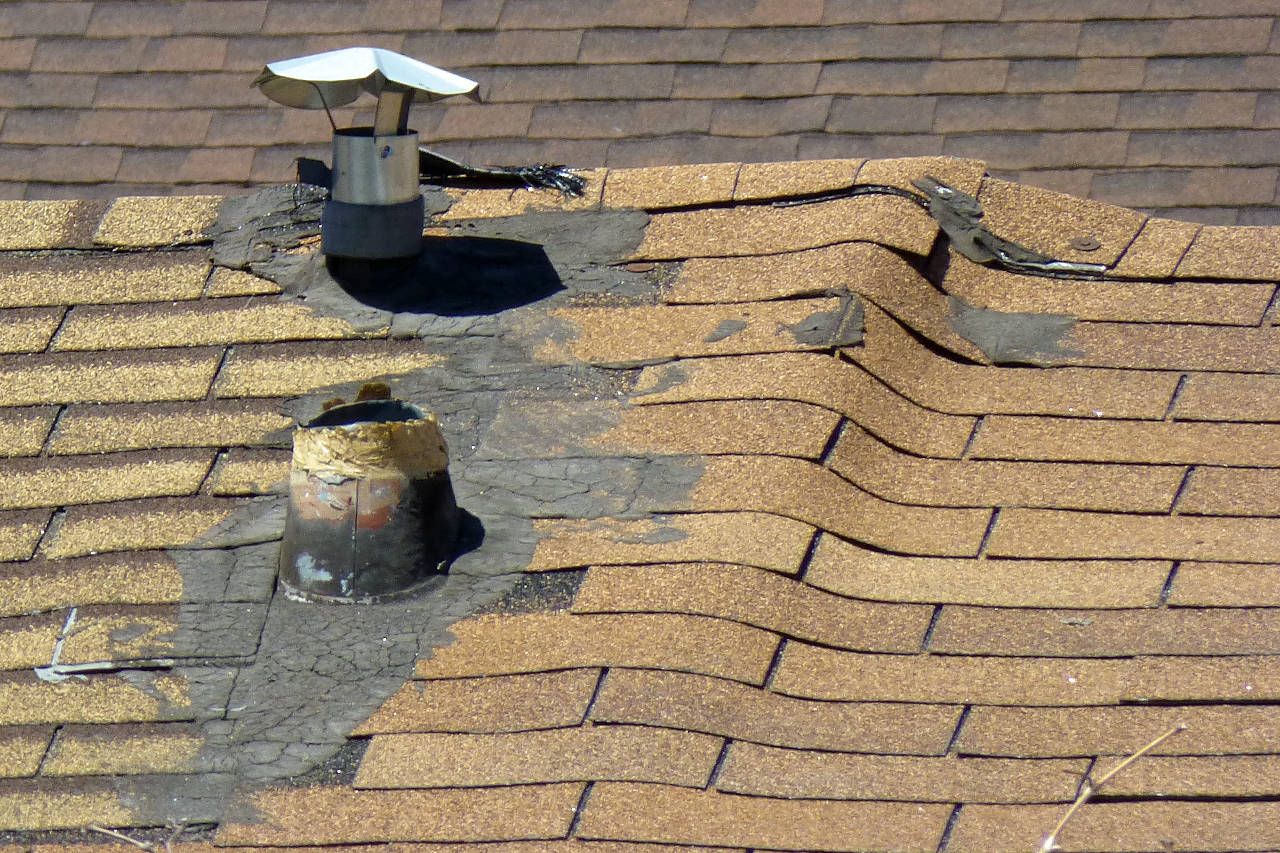 roof showing a significant buckle with a shingle separating