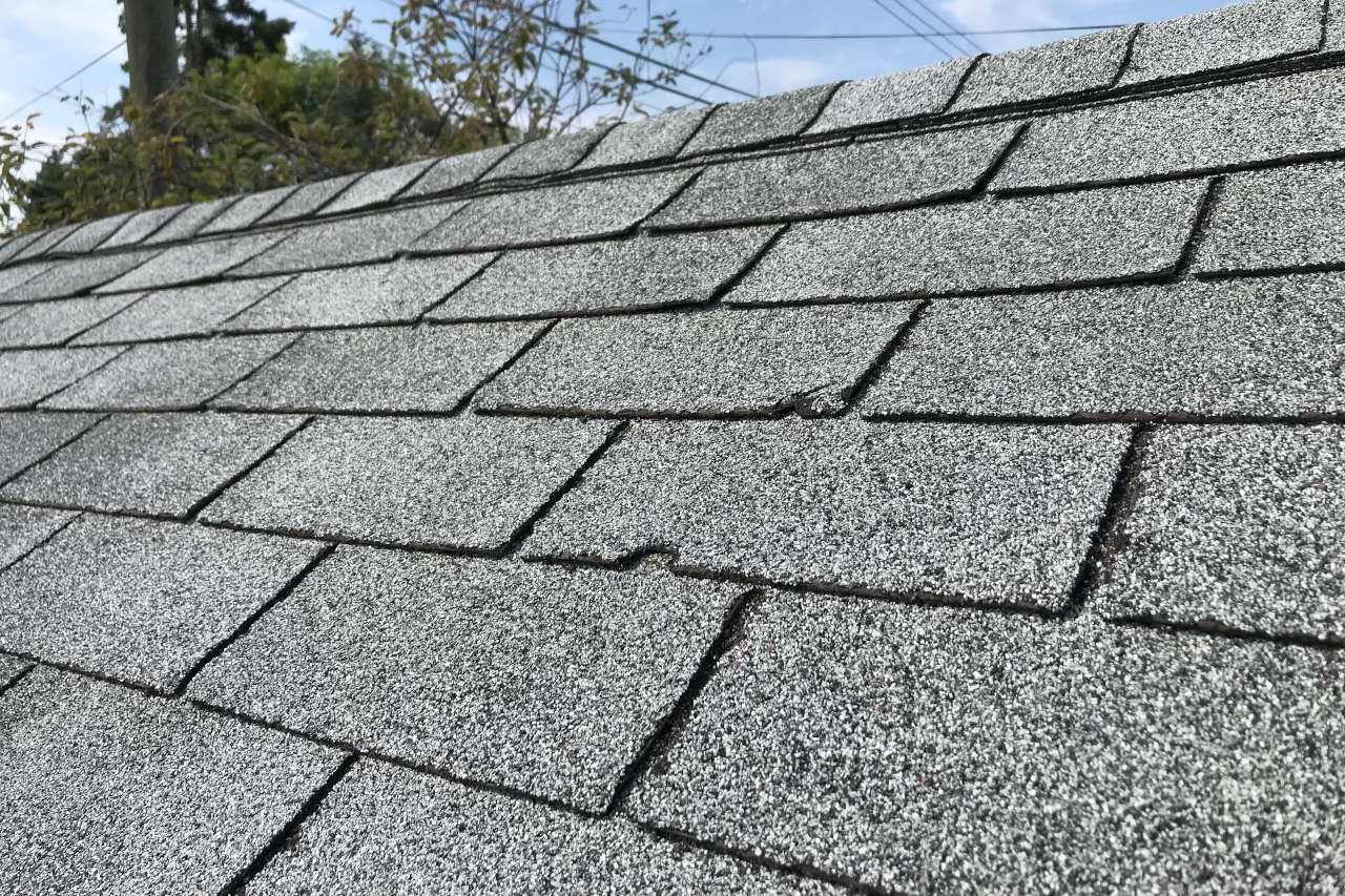 shingles with a large vertical crack spanning multiple courses